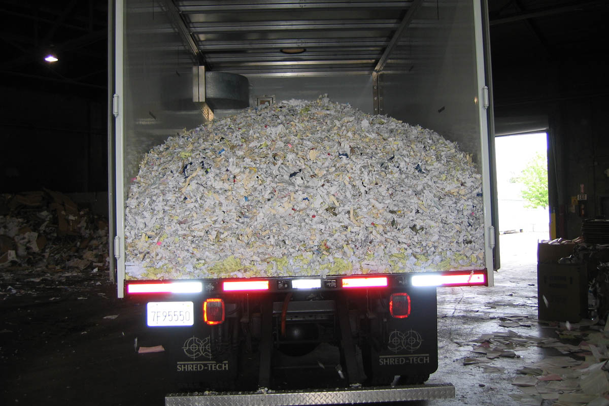 on site shredding service - mobile truck dumping shredded paper for recycling