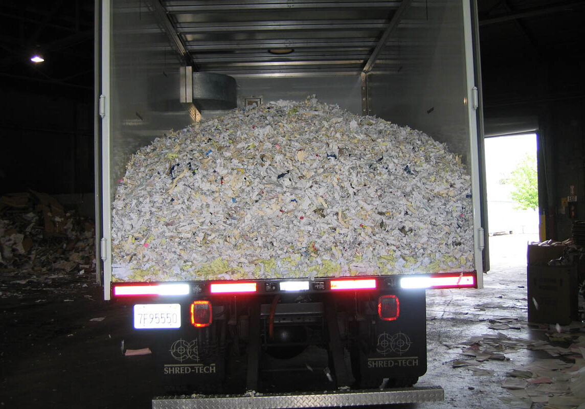 Mobile shredding truck dumping paper at recycling facility